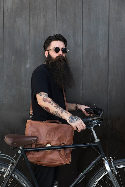 Handsome young man with bicycle standing in front of wooden black wall Free Photo