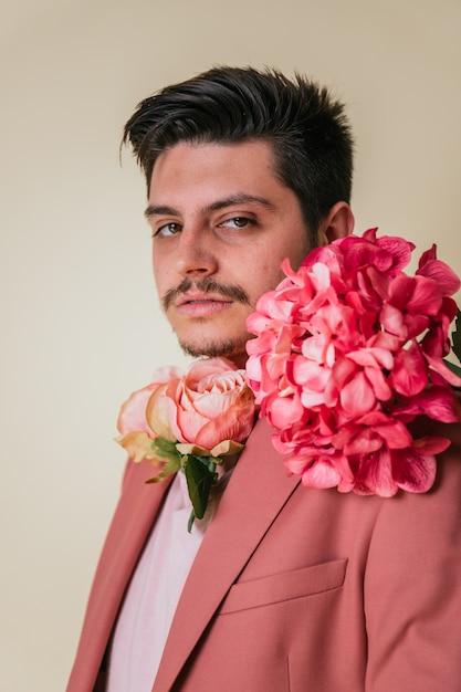 Красивый молодой человек с цветами на шее, в розовом костюме Premium Фотографии