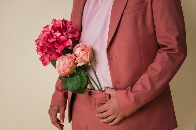 Красивый молодой человек с цветами в штанах, в розовом костюме Premium Фотографии