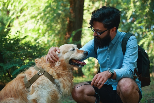 Handsome young man with golden retriver outdoors Free Photo