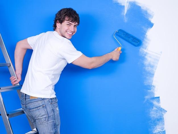 Bel giovane con un sorriso felice dipinto il muro Foto Gratuite