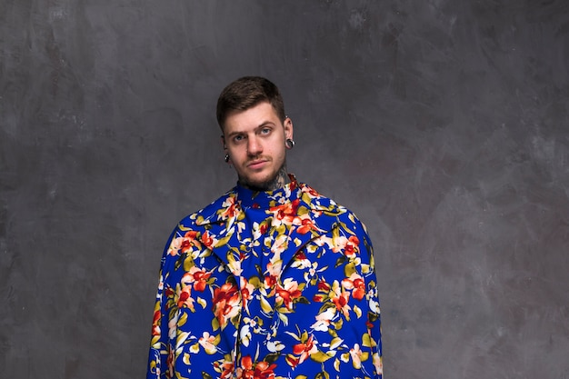 Handsome young man with pierced nose and ears wearing floral coat against grey backdrop Free Photo