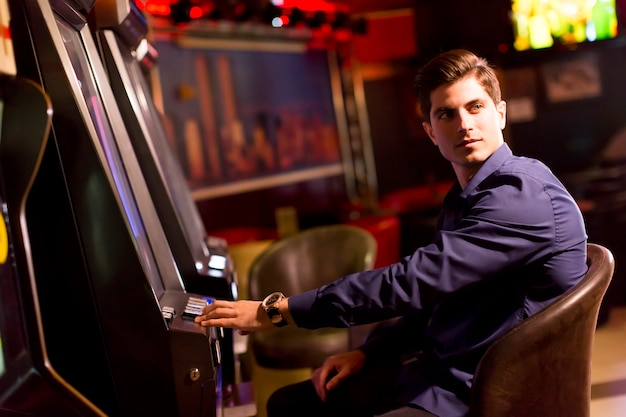 Handsome young man with slot machine in the casino | Premium Photo