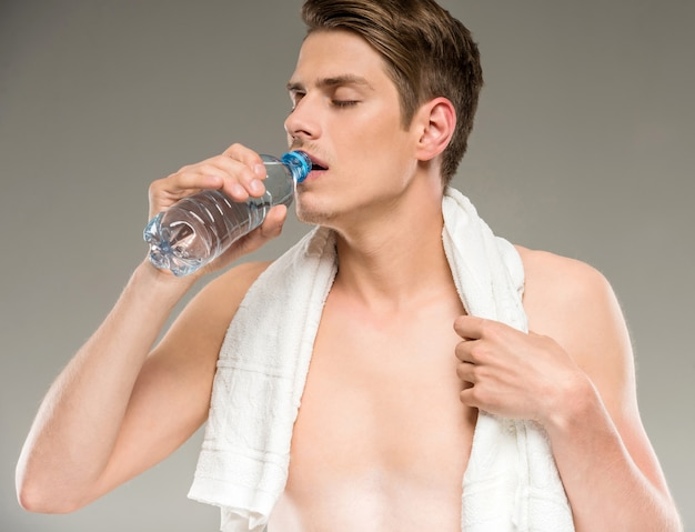 Handsome young man with towel on shoulders drinking water Premium Photo