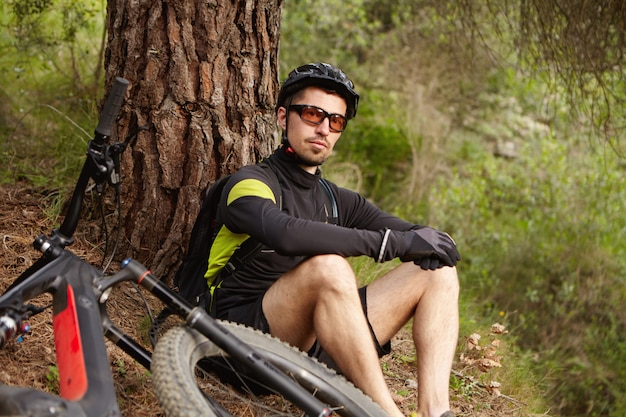 Handsome young professional rider wearing glasses and helmet sitting under tree, relaxing and admiring beautiful view after morning cycling workout on motor-powered booster bicycle on weekend Free Photo