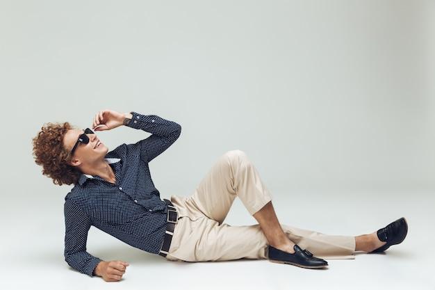 床にあるシャツに身を包んだハンサムな若いレトロな男 無料写真