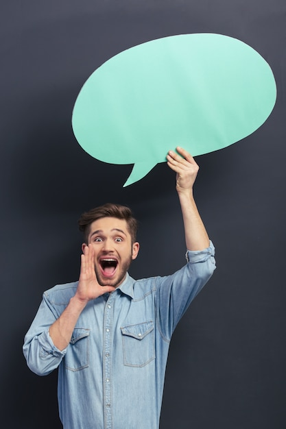 Handsome young student is holding a blue speech bubble. Premium Photo