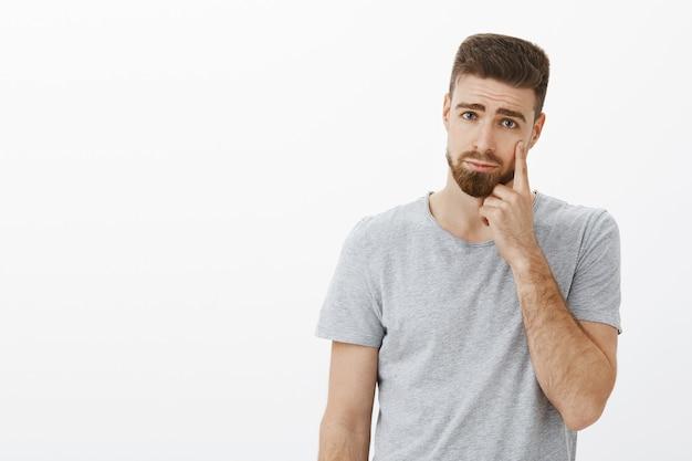 Красивый молодой тронутый парень с бородой с грустным и мрачным выражением лица, указывая на веко, как будто показывая слезу, выражающую сожаление или печаль, стоит недовольно плачет над серой стеной Бесплатные Фотографии