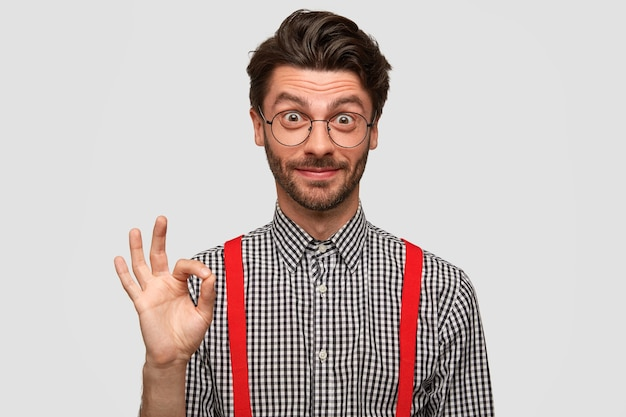 Handsome young unshaven man entrepreneur shows that everything is ok with hand, calms and tells you Free Photo
