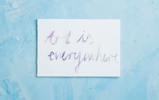 Handwritten 'art is everywhere' text on white paper over rough textured Free Photo