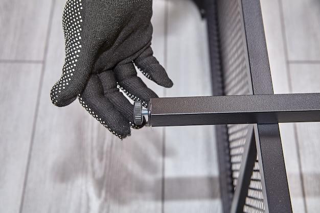 Handyman은 플랫 팩에서 가구 다리의 높이를 조정합니다. 프리미엄 사진