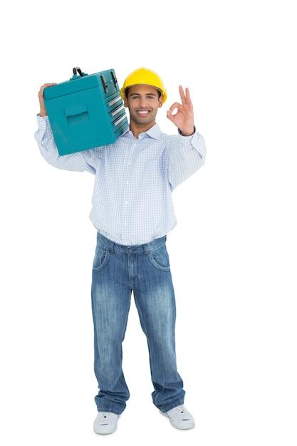 Handyman in hard hat with toolbox gesturing okay sign Premium Photo