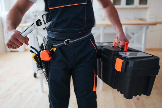Handyman holding toolbox and wrench in hands Premium Photo