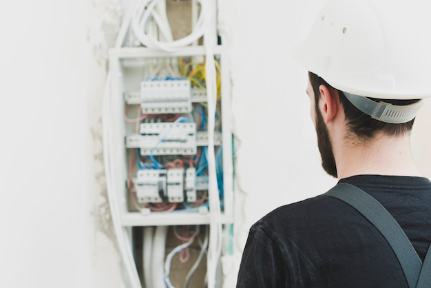 Handyman looking at switchboard Free Photo