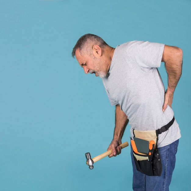 Handyman suffering from backpain holding hammer standing against blue background Premium Photo