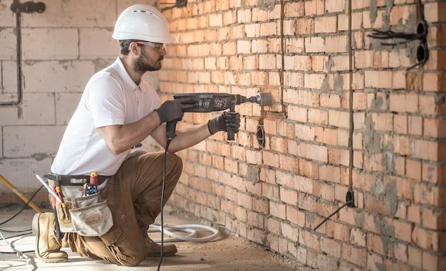 Разнорабочий использует отбойный молоток, для установки, профессиональный рабочий на строительной площадке. понятие об электрике и разнорабочем. Бесплатные Фотографии