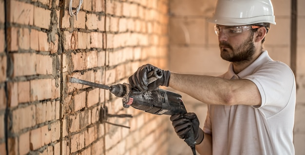 便利屋は、建設現場での設置、専門労働者のために削岩機を使用しています。電気技師と便利屋の概念。 無料写真