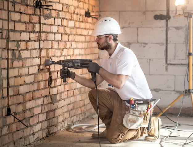 Tuttofare utilizza martello pneumatico, per l'installazione, operaio professionista in cantiere. il concetto di elettricista e tuttofare. Foto Gratuite