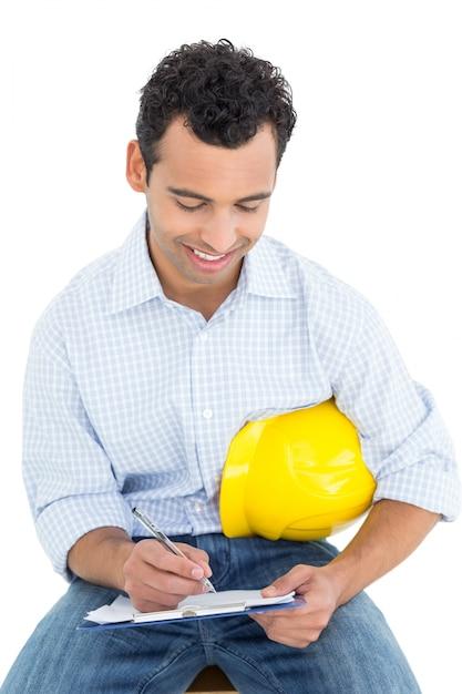 Handyman with yellow hard hat writing in clipboard Premium Photo