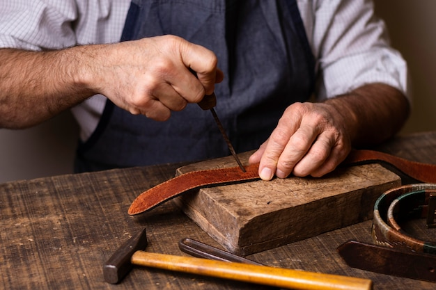 Handyman working on a leather belt front view Premium Photo