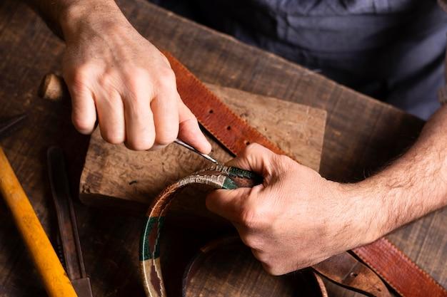 Handyman working on a leather belt Free Photo