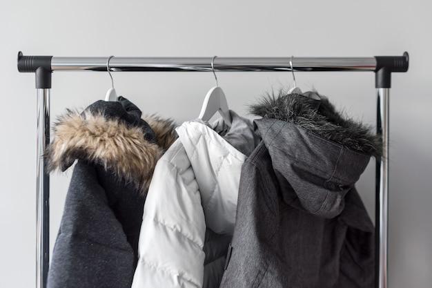Подставка вешалка с теплыми куртками. зимние куртки с меховым воротником висят на белых деревянных вешалках. Premium Фотографии