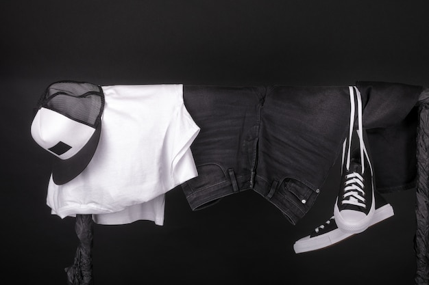 Hanging clothing. black and white sneakers, cap and jeans on clothes rack on black. Premium Photo