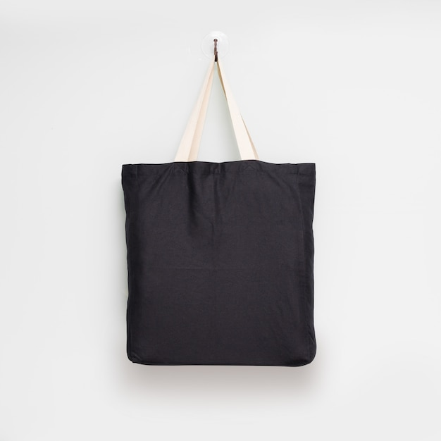 Hanging fabric bag on white wall background. Premium Photo