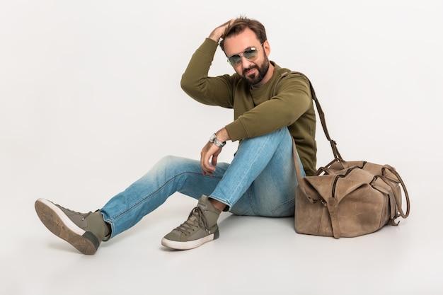 旅行バッグとスウェットシャツを着て、ジーンズとサングラスを身に着けている孤立した床に座っているハンサムなひげを生やしたスタイリッシュな男 無料写真