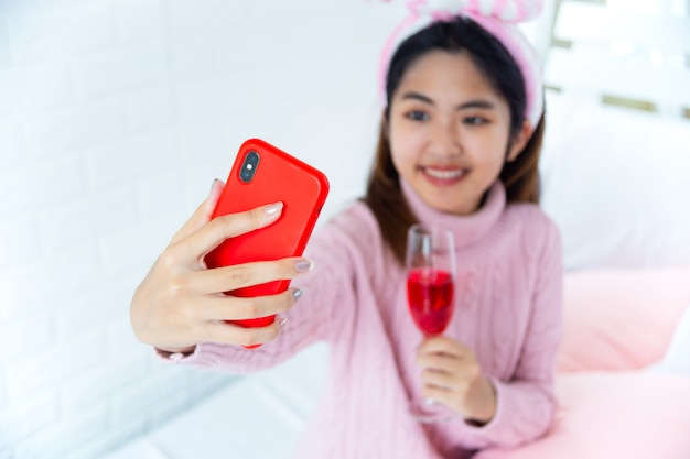 Happily teenager enjoying selfie with red wine in hand Free Photo