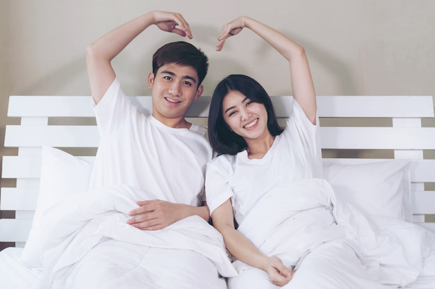 Happily young couple raise up arms make heart shape Free Photo