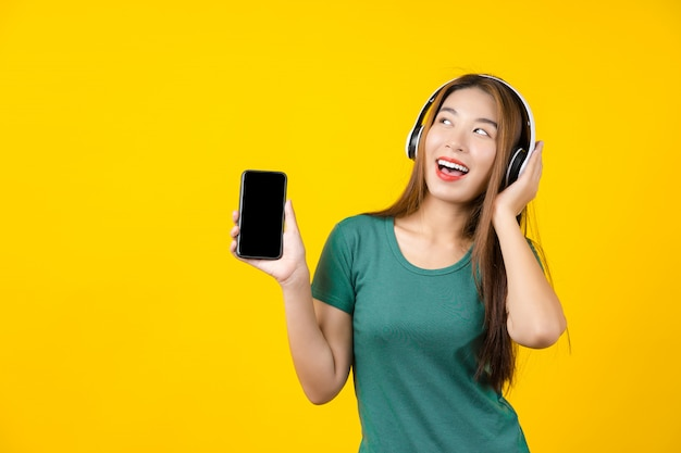 Happiness asian smiling young woman wearing technology wireless headphones for listening the music via smart mobile phone on isolated yellow wall, lifestyle and leisure with hobby concept Premium Photo