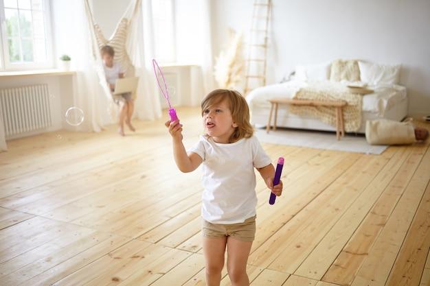 Felicità e concetto di infanzia spensierata. ritratto dell'interno di adorabile bambino femmina felice in t-shirt e pantaloncini in piedi nel mezzo del soggiorno moderno, divertendosi, soffiando bolle di sapone, Foto Gratuite