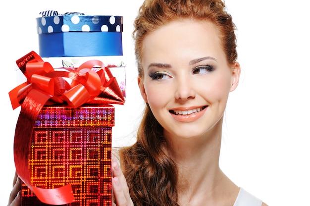 Счастье молодой девушки, смотрящей и держащей подарки на день рождения Бесплатные Фотографии
