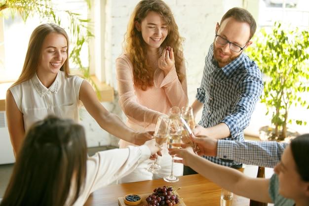 Счастье. люди звенят бокалами с вином или шампанским. Бесплатные Фотографии