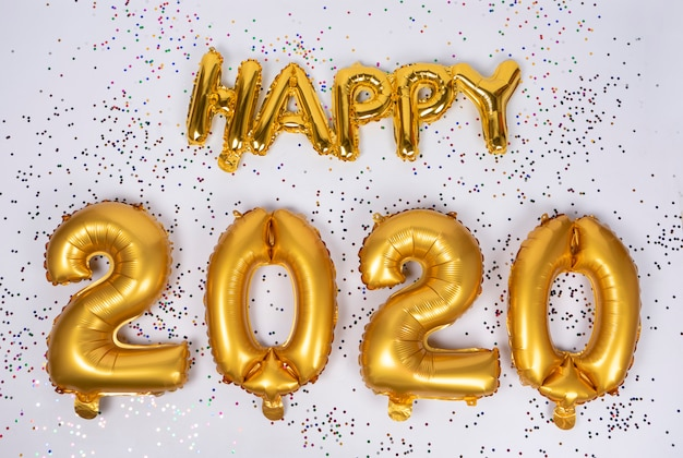 Happy 2020 lettering of frustrated gold balloons isolated with colorful confetti Premium Photo
