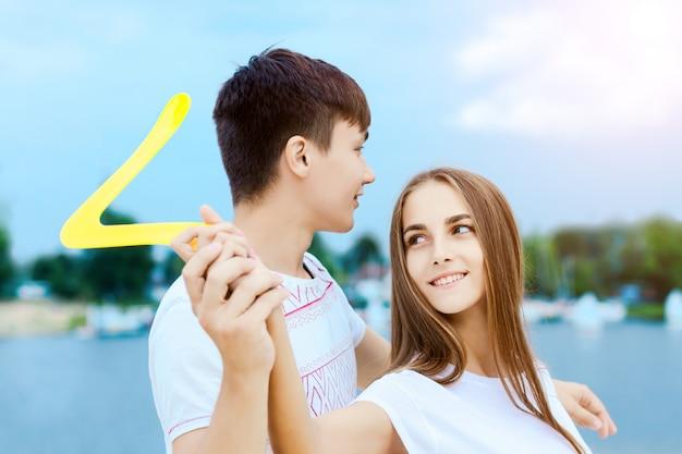 幸せなアクティブな笑顔のロマンチックなカップルはブーメランガールを遊んで砂ブナのゲームをスイングします Premium写真