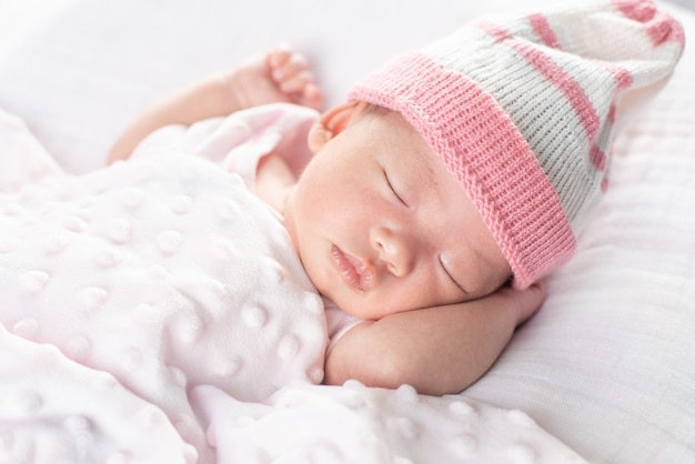 Happy adorable baby girl sleeping in crib. small kid having day nap in parents bed Premium Photo