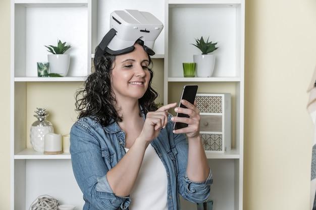 自宅でスマートフォンを使用して仮想現実の眼鏡で幸せな大人の女性 Premium写真