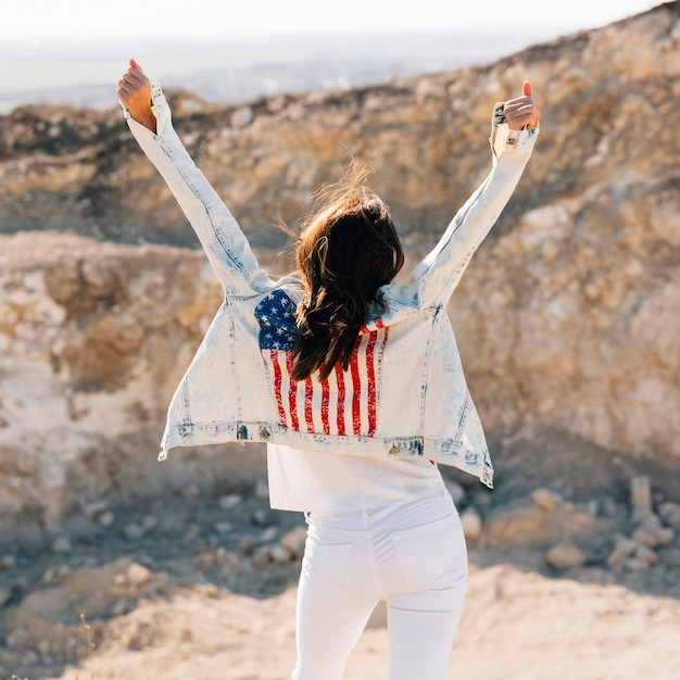 Happy adult woman raising hands on mountain Free Photo