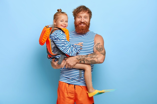 Счастливый ласковый отец несет на руках маленькую дочь, которая носит защитный спасательный жилет и ласты, собирается вместе плавать, наслаждаться летом, иметь рыжие волосы. рыжая семья в отпуске Бесплатные Фотографии