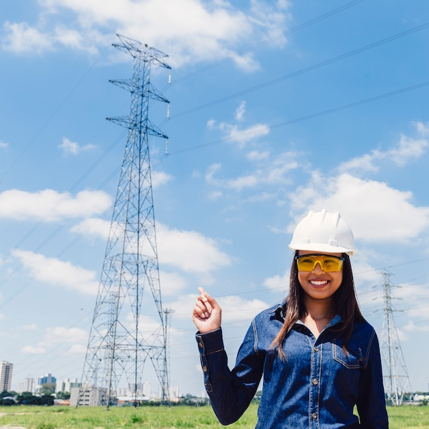 Happy african american lady in safety helmet pointing at high voltage line Free Photo