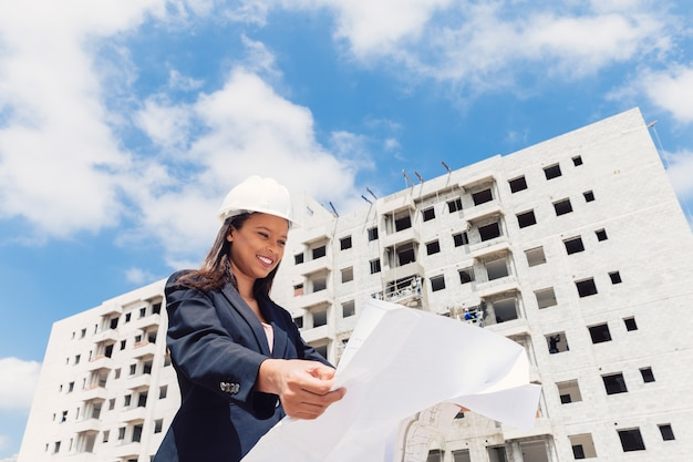 Happy african american lady in safety helmet with paper plan near building under construction Free Photo