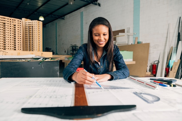 Happy African-American lady with big ruler and pen at table Free Photo