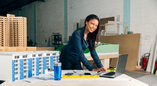 Happy african-american lady with laptop and model of building on table Free Photo