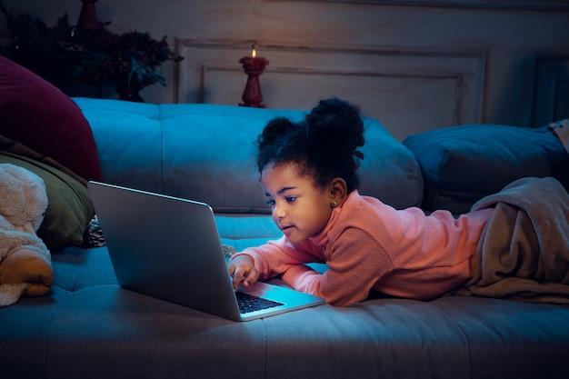 ラップトップと家庭用デバイスでビデオ通話中に幸せなアフリカ系アメリカ人の少女は、喜んでいるように見えます 無料写真