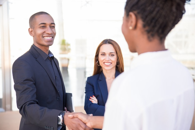 Happy african american male manager shaking hand of partner Free Photo