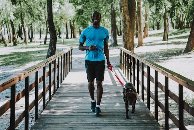 Happy african american man jogging on footbridge Premium Photo