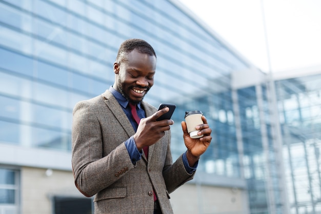 Happy african american man looks lucky reading something in his smartphone Free Photo