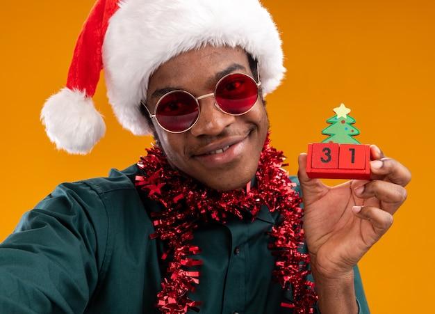 Uomo afroamericano felice in cappello della santa con gli occhiali da sole d'uso della ghirlanda che tiene i cubi del giocattolo con la data del nuovo anno sorridente che sta sopra la parete arancione Foto Gratuite